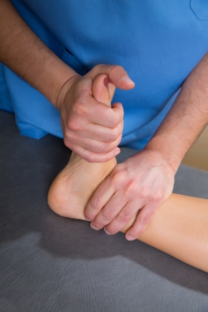 mobilization: Ankle physiotherapy treatment with therapist hands in woman feet