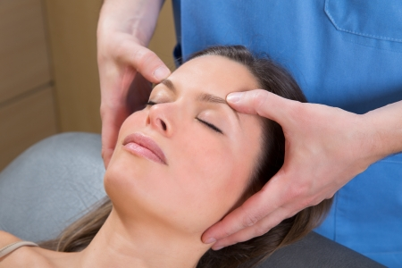 reflexology: facial massage relaxing therapy on woman face with therapist hands Stock Photo
