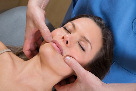 reflexology: Facial tuina massge therapy on beutiful woman face by therapist hands