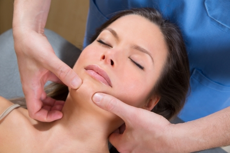tuina: Facial tuina massge therapy on beutiful woman face by therapist hands