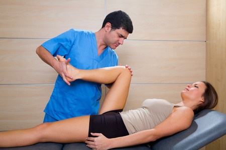 hip mobilization therapy by physiotherapist in hospital to beautiful woman Stock Photo - 19615016