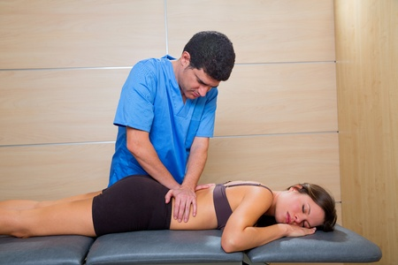 Massage therapy by physiotherapist on back torso to beautiful woman relaxed photo