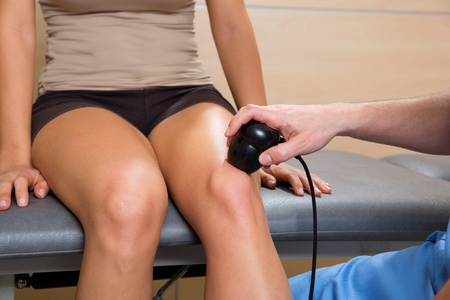 Ultrasonic therapy machine treatment doctor and woman patient on her knee photo