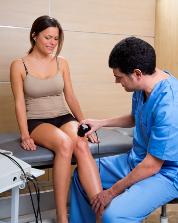 ultrasonic: Ultrasonic therapy machine treatment doctor and woman patient on her knee