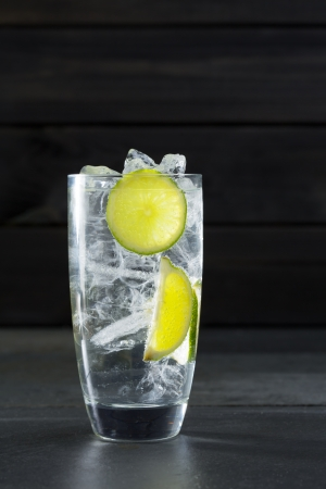 tonic: Gin tonic cocktail with lima and ice cube on black slate stone background