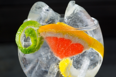 Gin tonic macro cóctel con lima limón y pomelo, detalle en negro Foto de archivo
