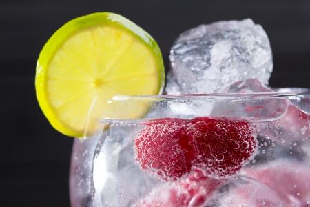 Gin tonic cóctel con rodaja de lima y frambuesa hielo macro primer plano en negro Foto de archivo