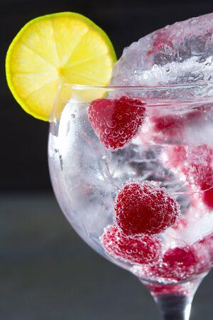 Gin tonic cocktail with raspberry lima slice and ice macro closeup on black photo