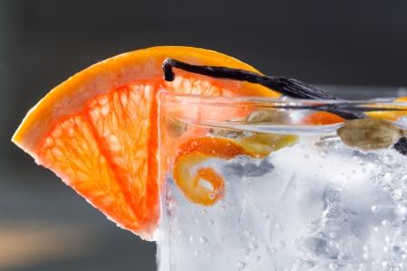 Gin tonic cocktail macro with ice grapefruit cardamom vanilla closeup on black photo