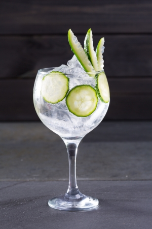 Gin tonic cocktail with cucumber and ice on black background photo