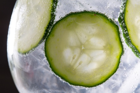 Gin tonic cocktail with cucumber and ice  macro closeup on black photo