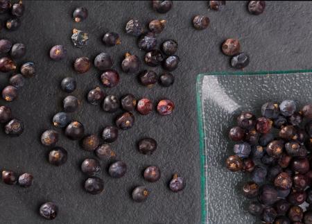 enebro: bayas de enebro detalle macro primer plano sobre fondo de piedra de pizarra negro