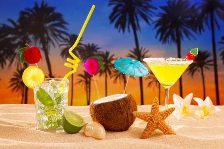 caribbean drink: beach cocktail sunset on palm tree sand mojito margarita coconut Stock Photo