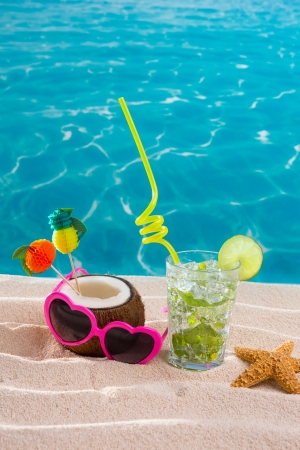 Mojito cocktail on beach sand with coconut and sunglasses in summer vacation photo