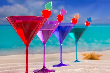 riviera: colorful cocktail in a row with cherry on tropical sand beach of turquoise sea Stock Photo