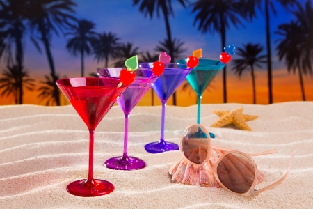 colorful cocktail in a row with cherry on sand beach palm trees sunset photo