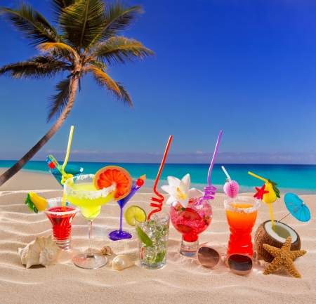 Colorful tropical cocktails at beach on white sand and palm tree photo