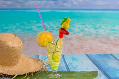Lemon lime cocktail mojito on tropical turquoise beach on blue wood photo