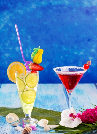 Lemon Mojito and red Margarita cocktails in Caribbean blue wood with flowers and seashells photo