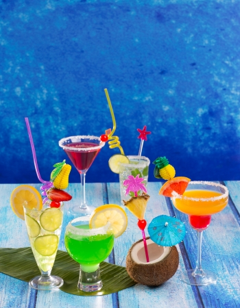 Colorful varied tropical Cocktails in tropical blue wood with coconut mojito pepermint margarita photo