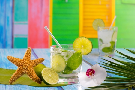 Cuban Mojito cocktail in tropical colorful house on blue wood with flowers and starfish photo