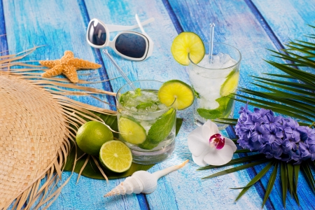 Cuban Mojito cocktail in tropical blue wood with sunglasses flowers and starfish photo
