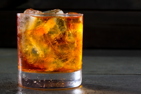 intoxicant: Whiskey whisky on the rocks on glass over gray black background