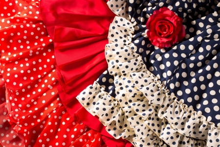 fiesta popular: Flamenco dresses in red and blue with spot with red rose typical from Spain Espana Stock Photo