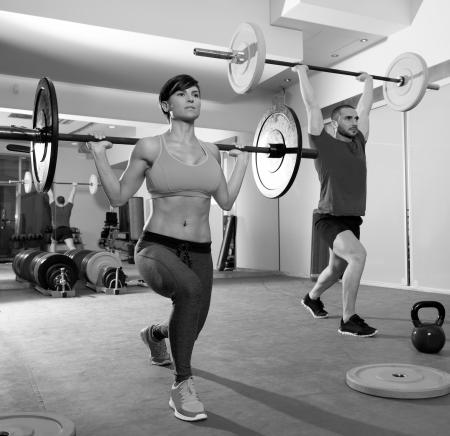 levantamiento de pesas: Crossfit gym barra de levantamiento de pesas de la mujer y del grupo del hombre de entrenamiento