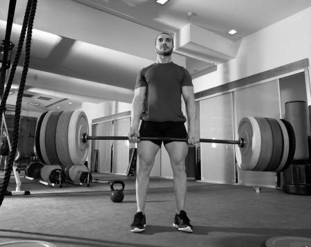 lifting: Crossfit fitnessruimte zwaar gewicht tillen bar door sterke man workout