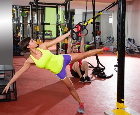 gymnasium: Crossfit fitness TRX training exercises at gym woman and dip rings man workout