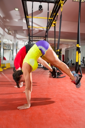pushup: Crossfit fitness TRX training exercises at gym woman and man push-up pushup
