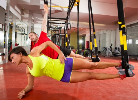 Crossfit fitness TRX training exercises at gym woman and man side push-up workout Stock Photo