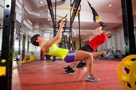 group fitness: Crossfit fitness TRX training exercises at gym woman and man push-ups workout