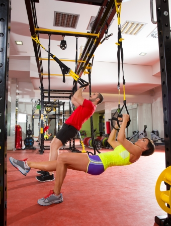 Crossfit fitness TRX training exercises at gym woman and man push-ups workout photo