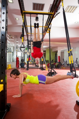 pushup: Crossfit fitness TRX training exercises at gym woman push-up and dip rings man workout Stock Photo