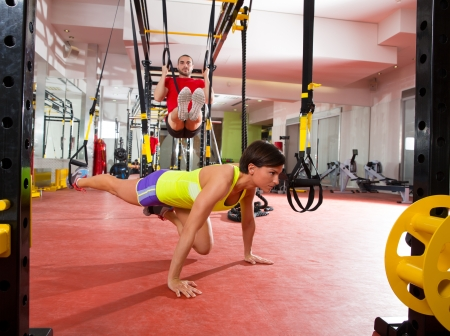 fit: Crossfit fitness TRX training exercises at gym woman push-up and dip rings man workout Stock Photo