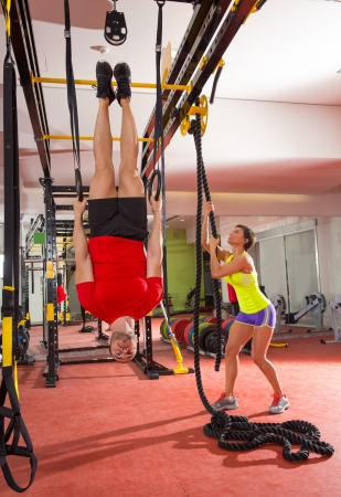 Crossfit fitness dip ring man workout upside down at gym dipping ans woman with rope photo