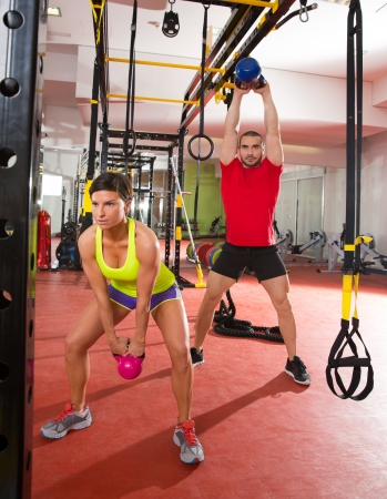 Crossfit fitness Kettlebells swing exercise man and woman workout at gym photo