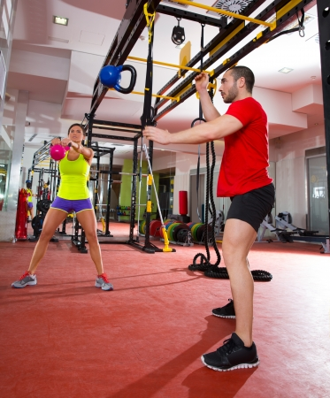Crossfit fitness Kettlebells swing and flying exercise man and woman workout at gym photo