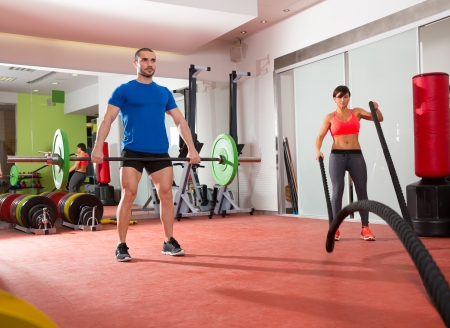 battling: Crossfit fitness gym weight lifting bar man and woman battling ropes workout Stock Photo