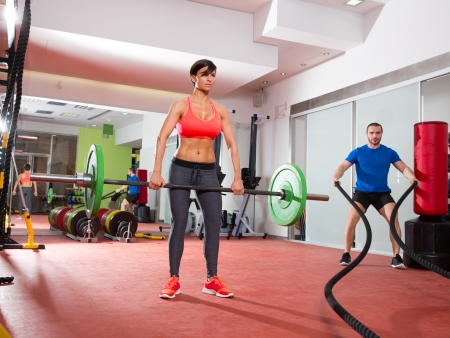 battling: Crossfit fitness gym weight lifting bar woman and man battling ropes workout