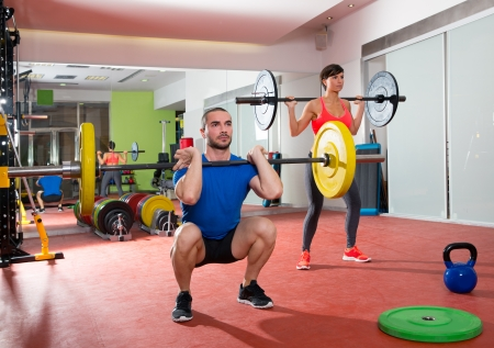 man lifting weights: Crossfit fitness gym weight lifting bar by woman and man group workout Stock Photo