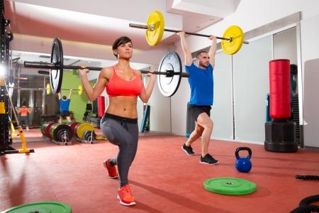 女と男のグループ トレーニングによって Crossfit フィットネス ジム重量挙げバー