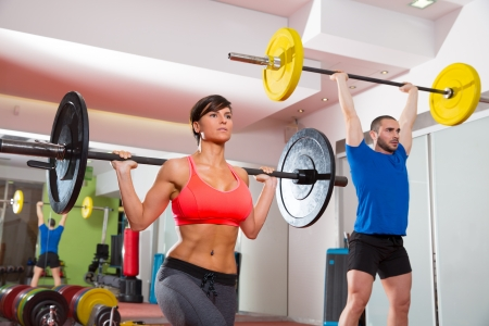 gymnasium: Crossfit fitness gym weight lifting bar by woman and man group workout Stock Photo