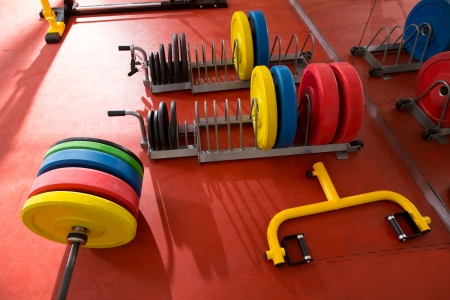adjustable dumbbell: Crossfit fitness gym weight lifting bar colorful equipment on red floor Stock Photo