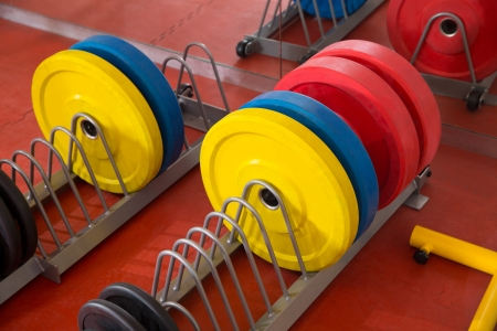 cross bar: Crossfit fitness gym weight lifting bar colorful equipment on red floor Stock Photo