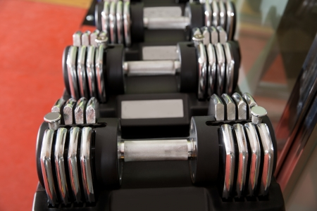 Adjustable weight dumbbells in a row with selective focus in foreground photo