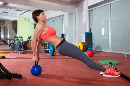 Crossfit fitness woman push ups with Kettlebell rear pushup exercise Stock Photo