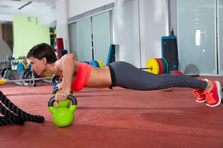 Crossfit fitness woman push ups Kettlebells pushup exercise at gym workout photo